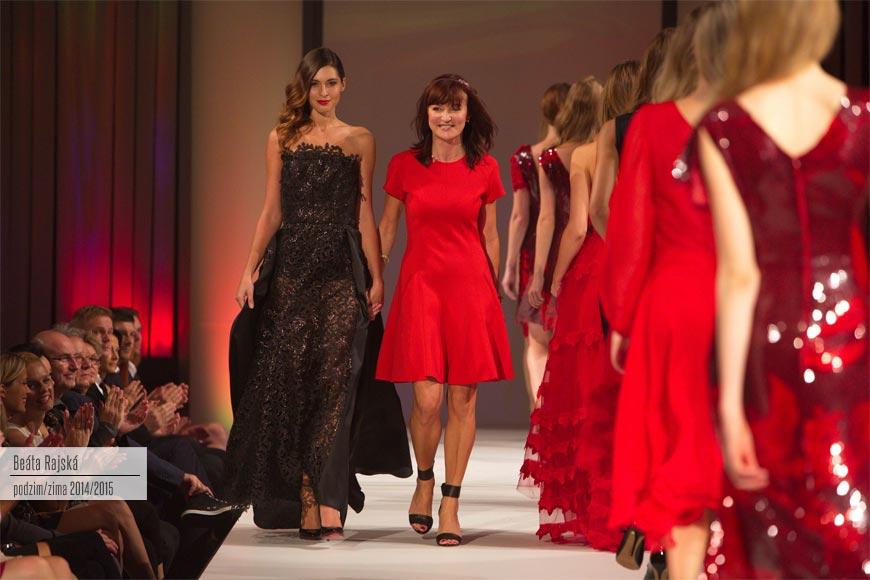 Módní návrhářka Beata Rajská v červeném modelu ze své kolekce a s mladistvým účesem s čelenkou. Vede se za ruku s modelkou, která předvádí vrcholný kousek z její kolekce pro podzim a zimu 2014/2015 – krajkové černé večerní šaty.